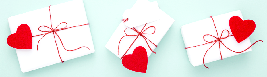 Gifts wrapped in white wrapping paper with red hearts and red string on a light blue background