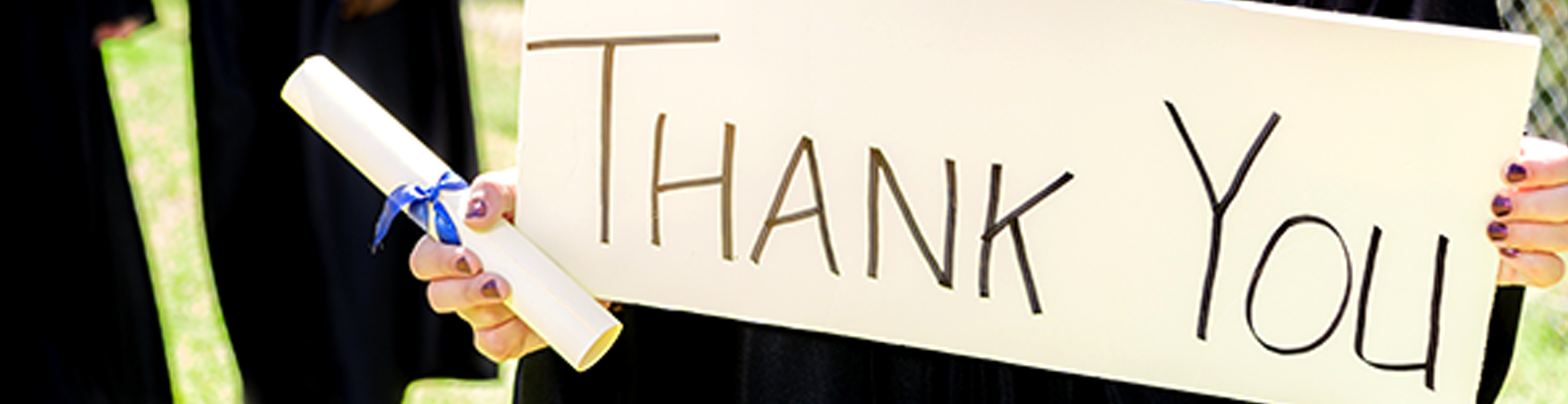 graduate holding a thank you sign