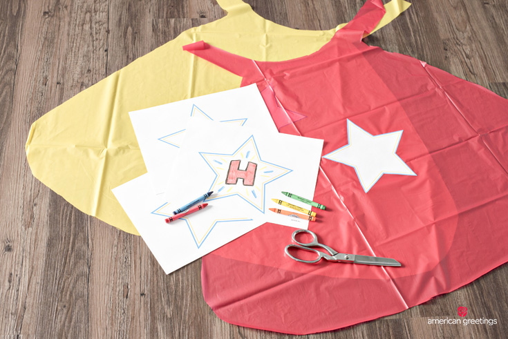 capes made from plastic tablecloth and personalized with star emblem