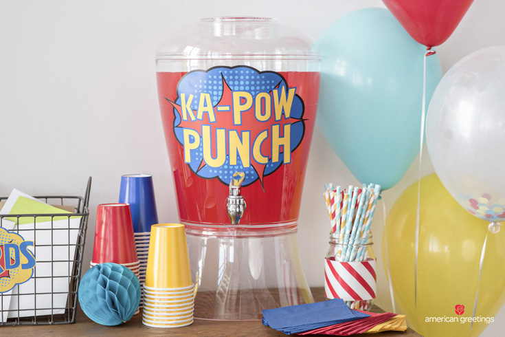 table with beverage station with KAPOW sign added, straws and plastic glasses