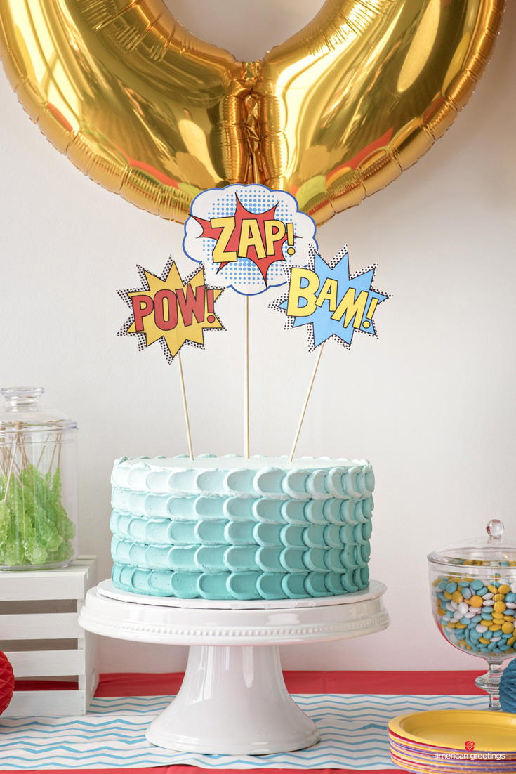 POW ZAP BAM starbust printables taped to toothpicks on top of the cake