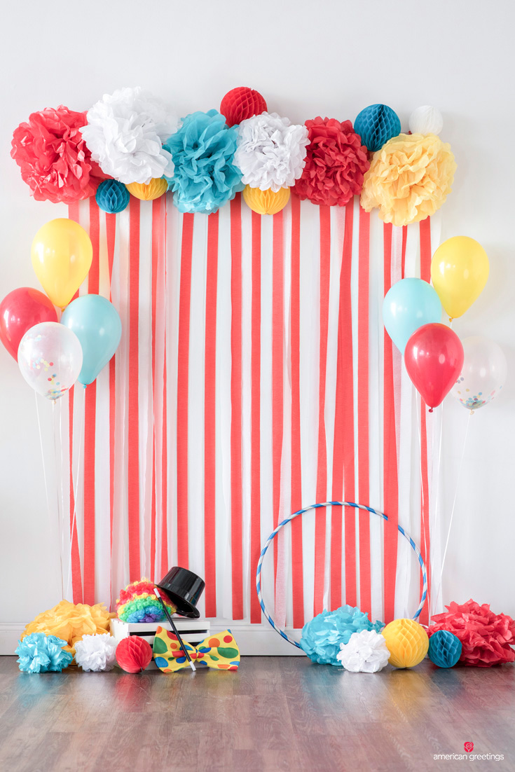photo backdrop framed with tissue paper pom poms, honeycomb balls, and balloons