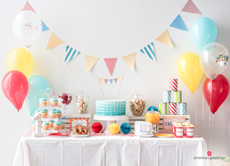 food table coverd with white plastic tablecloth, decorated with pennant banner, balloons