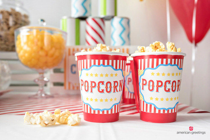 popcorn cups with free printable labels printed on sticker sheets and attached