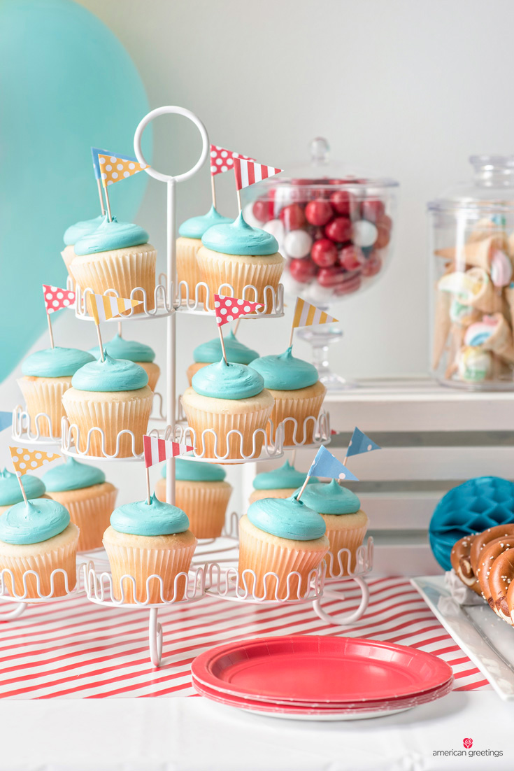 cupcakes topped with pennants attached to toothpicks