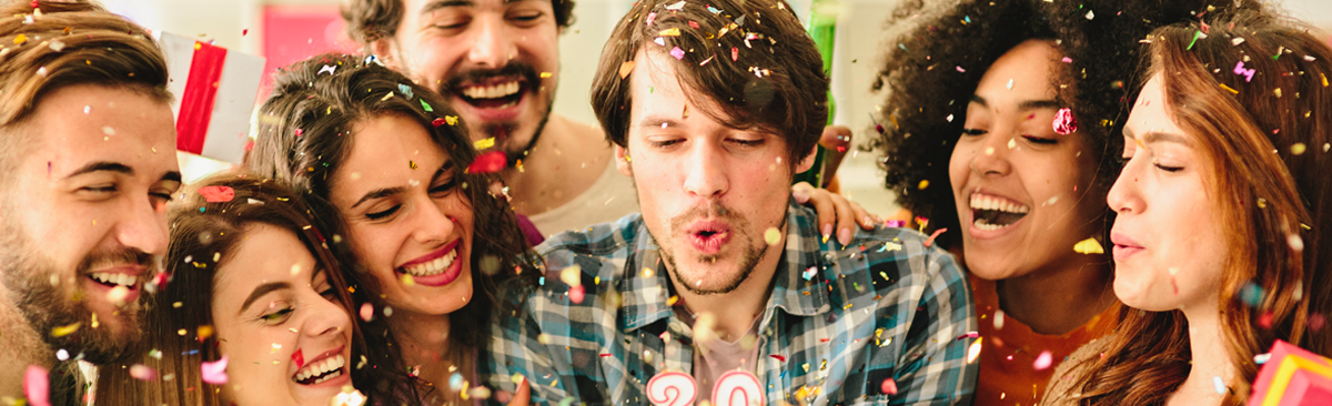 Group of people celebrating a 30th birthday by blowing out candles on a cake