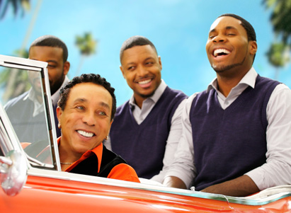 Smokey Robinson riding in a convertible car with his band