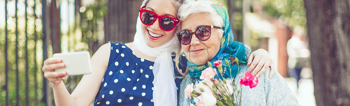 Woman with grandma hanging out in the park and taking a selfie