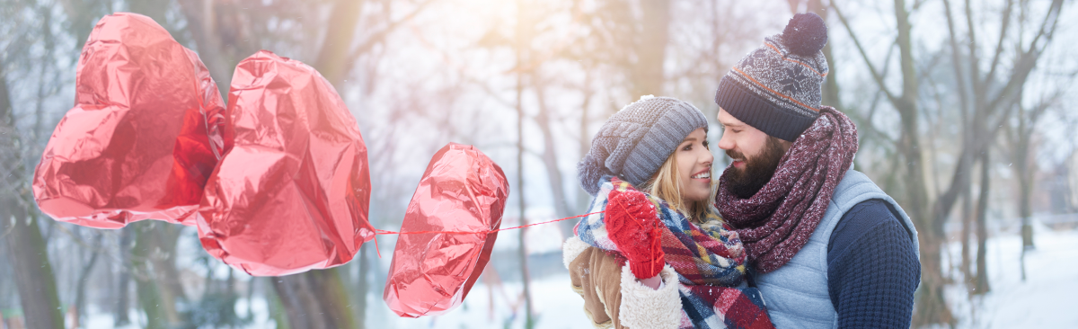 Couple in love holding heart balloons in the snow