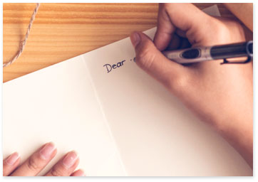 Hand holding a pen and writing a message in a card - Get tips on what to write
