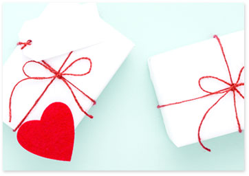 Gifts - Two gifts wrapped in white wrapping paper with red string and red hearts. View gifiting ideas