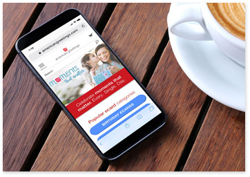 American Greetings website on mobile phone next to cup of coffee - Learn more about what's new