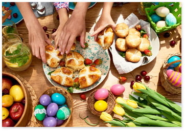 Seasonal inspiration - Spring ideas - Family and friends reaching for buns on a wood table with fresh flowers, fruit and colored eggs.