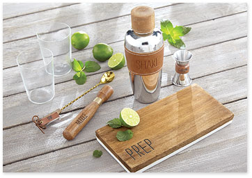 Martini shaker, bar tools, cutting board, glassses and limes on wood table - Shop gifts for him
