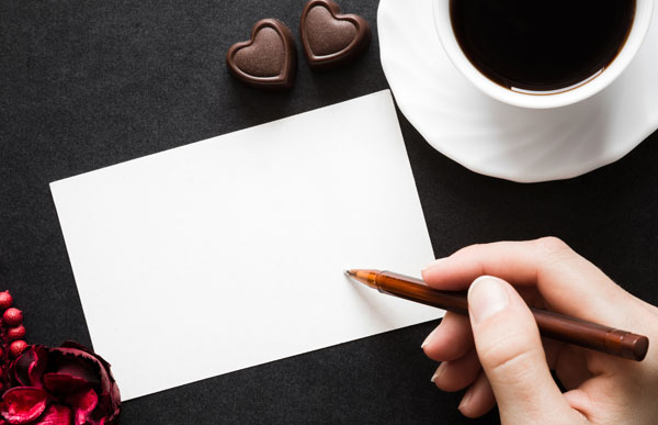 Hand holding a pen beginning to write a note with cup of coffee and 2 chocolate hearts