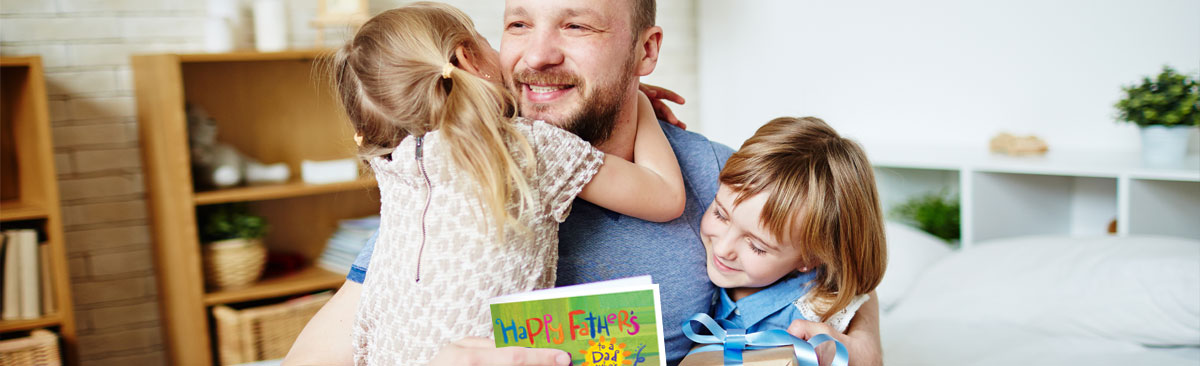 Dad hugging young daughters and holding a Father's Day Card