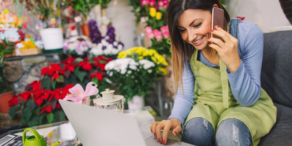 Girl making a purchase online with cell phone in an outdoor garden setting