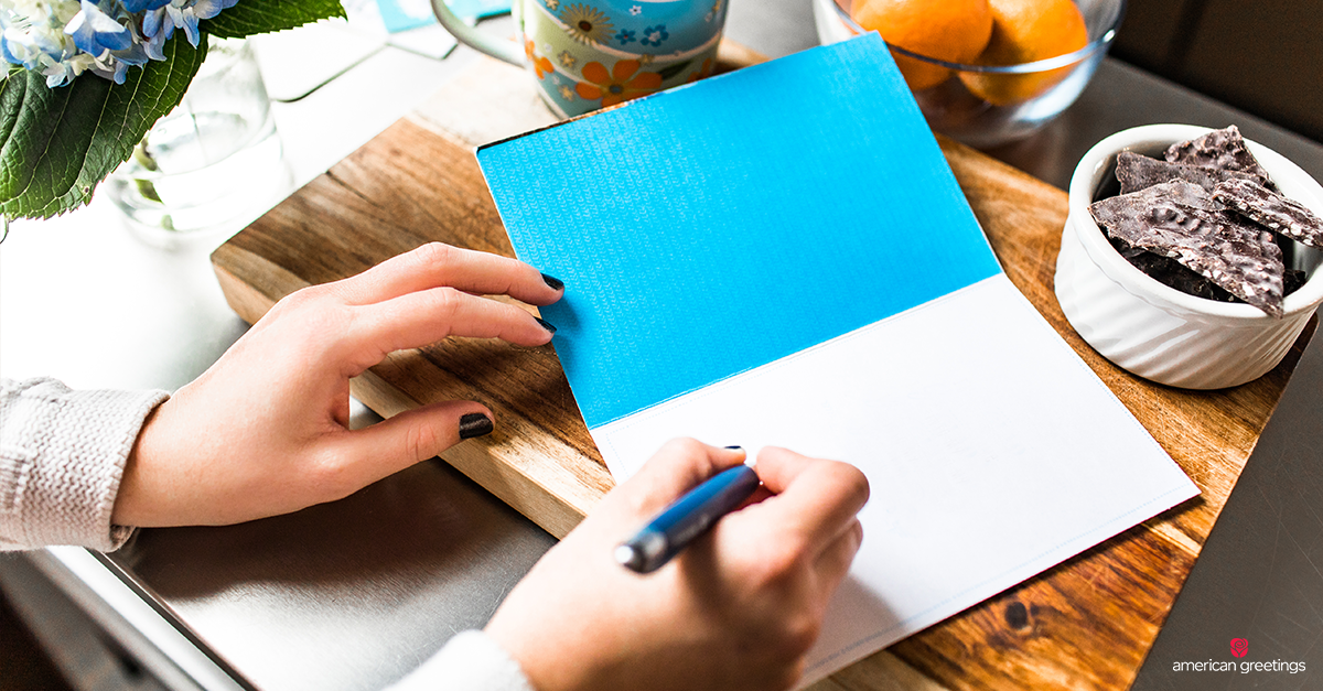 Writing a note in a blue covered card