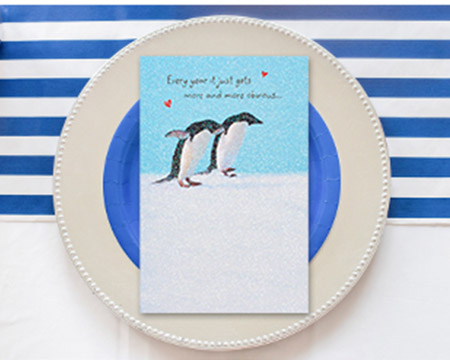 Greeting card with penguins on a plate
