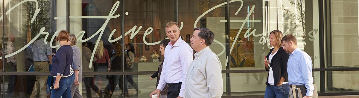 People walking past the first-floor windows of the American Greetings Creative Studios entrance in Westlake, Ohio.