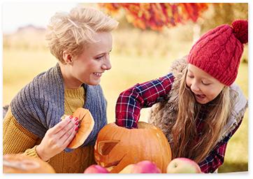 Mother and daughter making a Halloween pumpkin