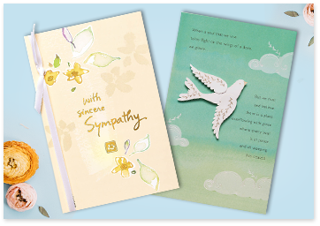 Sympathy greeting cards near some pink and yellow roses