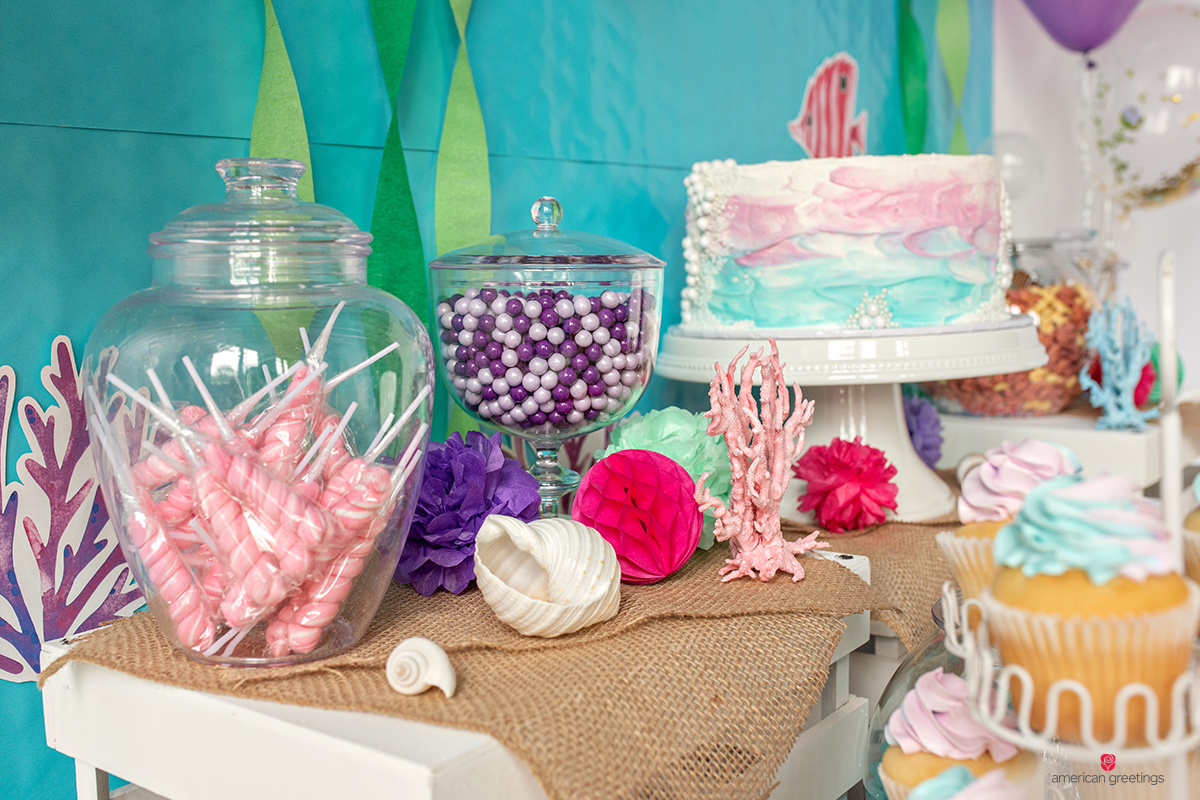 Fishbowls filled with white and purple candies and pink twist lollipops