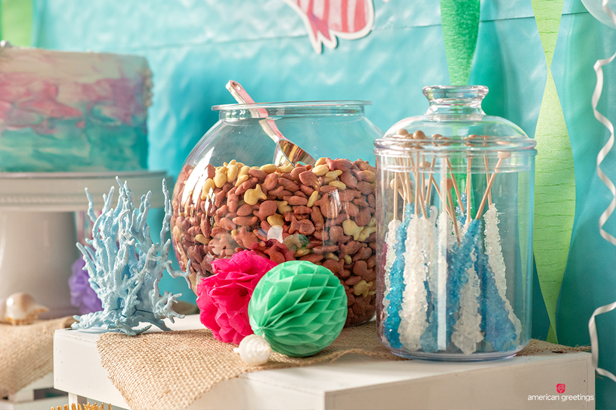 Jars filled with pink and white fish crackers and blue and white rock candy