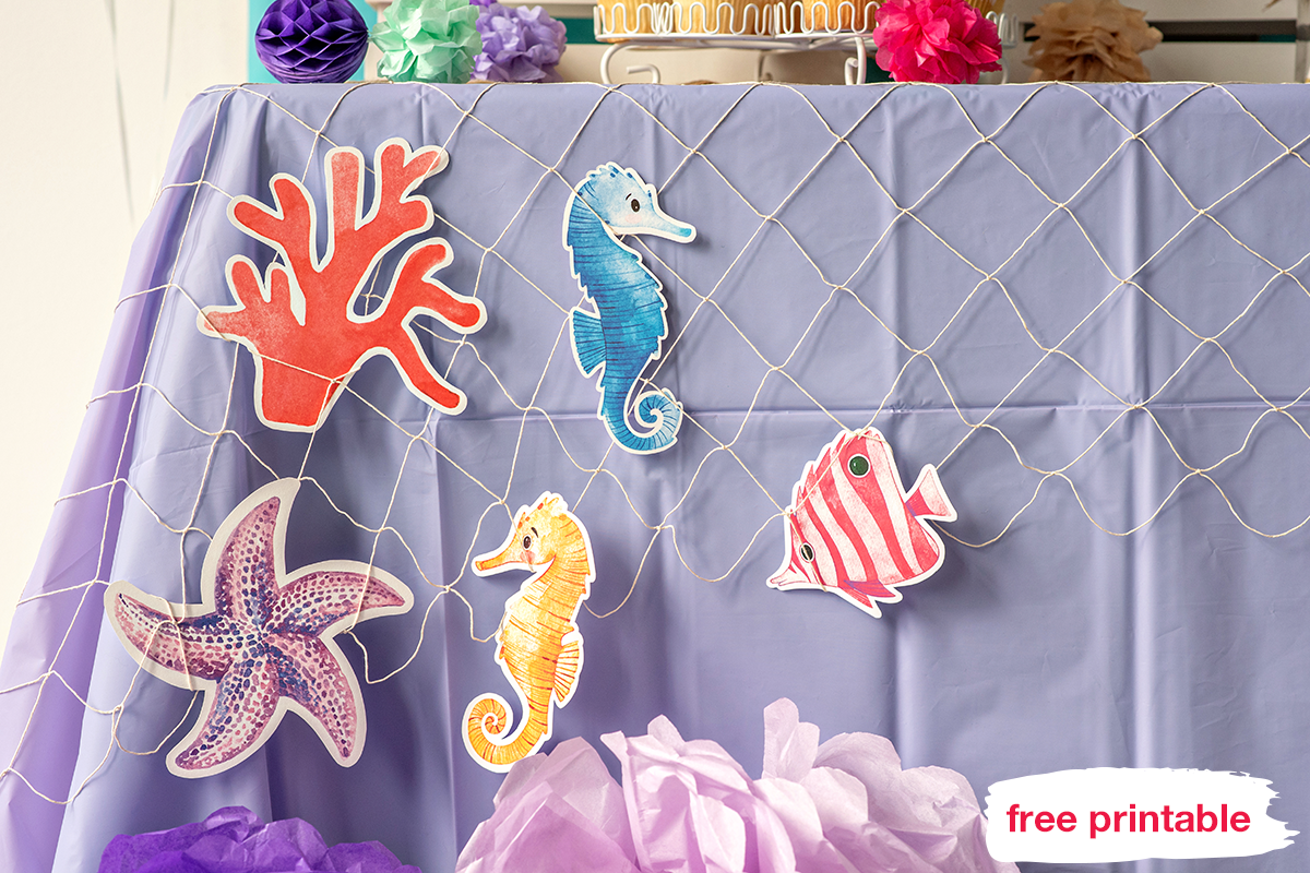 Printables seahorses, sea stars, fish, and corals hanging on the table cloth