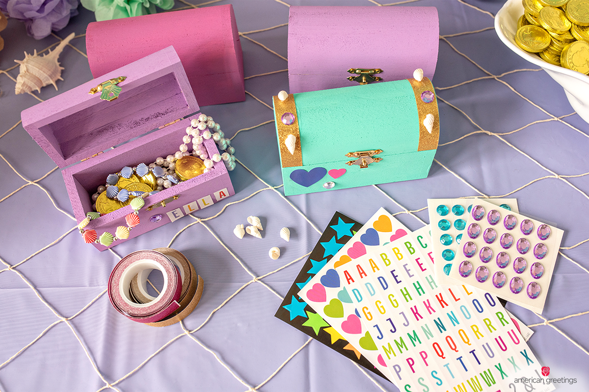 Plain treasure boxes, paint, stickers, glitter tape, and plastic shells and gems to glue on