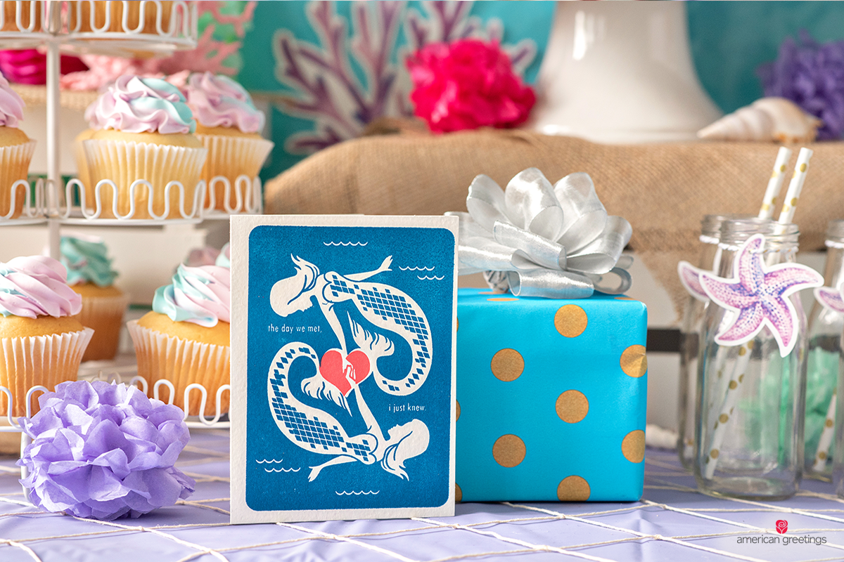 Blue mermaids greeting card next to a blue dotted wrapped gift