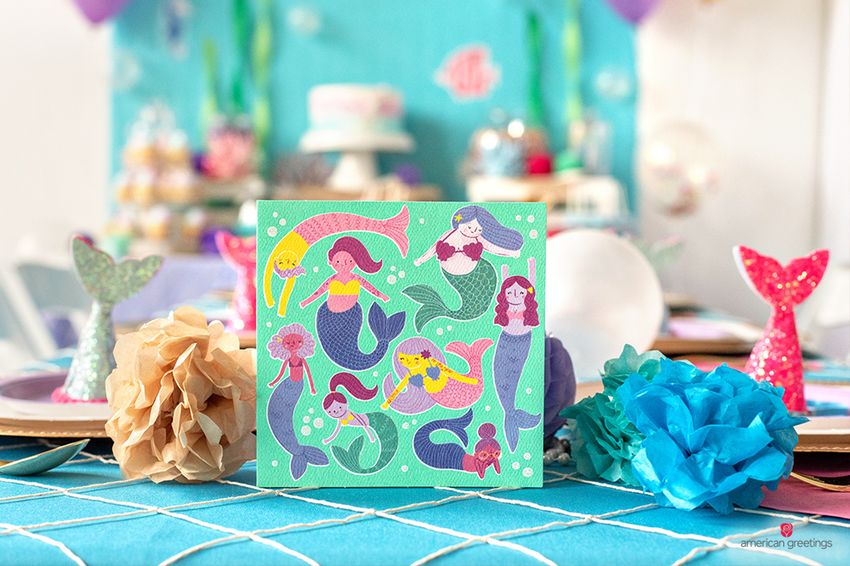 Mermaids greeting card next to balloons and pom-poms