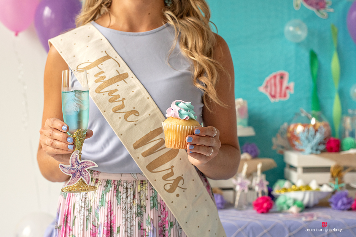 Young woman wearing a Future Mrs. sash and holding a cupcake and a champagne glass