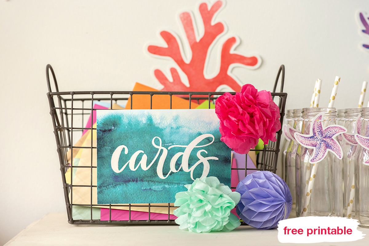 "Basket with the printable ""cards"" sign decorated with pom-poms"