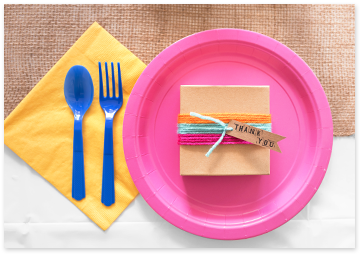 Purple plate next to a yellow napkin with blue plastic tableware