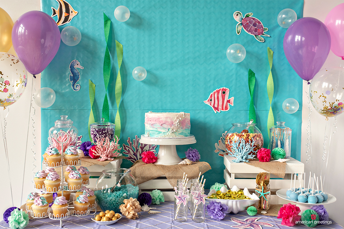 DIY mermaid party themed backdrop behind the food table