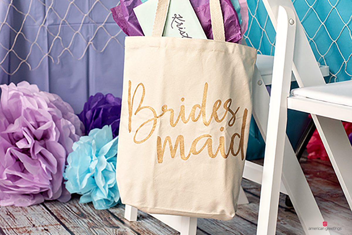 Tote bags for the bridesmaids hanging on a chair