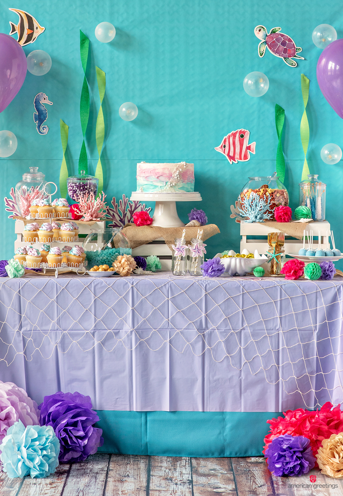 Food table layered with both turquoise fabric and a lavender plastic tablecloth, topped with netting and accented with floor pom-poms