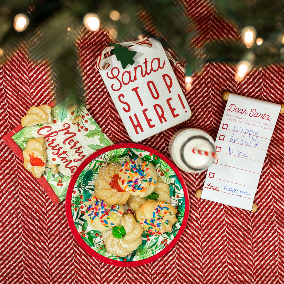 Milk and colorful cookies with a special letter dedicated to Santa near the Christmas tree.