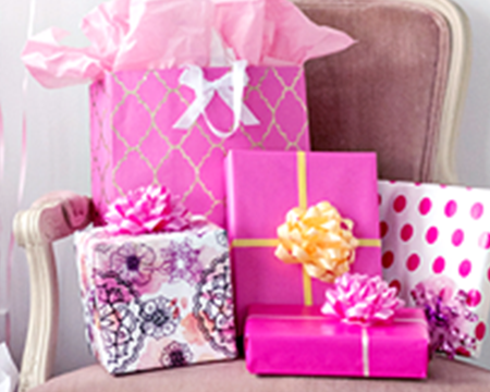 Stack of pink-wrapped gifts on a chair