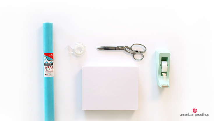 A picture of gift wrapping supplies with blue reversible wrapping paper, boxed item, tape and scissors.