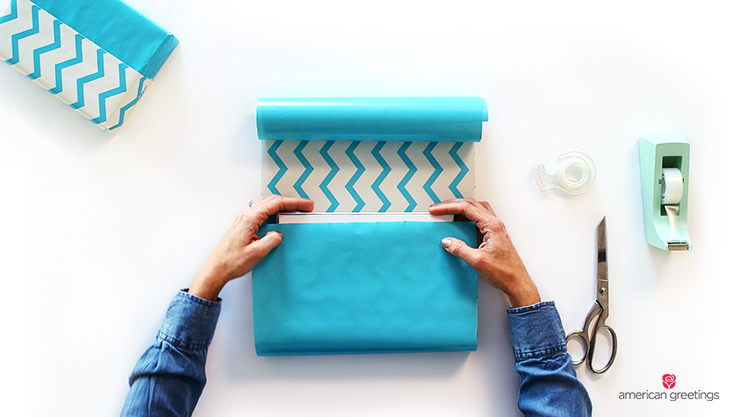 A model's hands are shown wrapping the blue reversible gift wrap around a boxed gift next to tape and scissors.