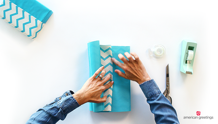The models's hands are showing you how to crease the blue reversible gift wrap with your fingernail.