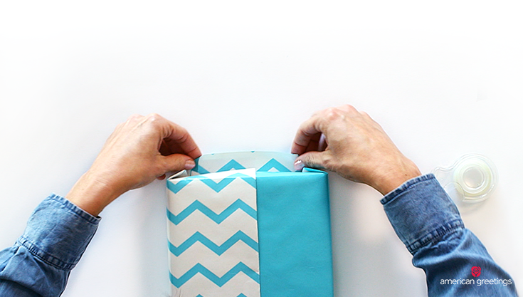 A close up of the model hands folding the blue zig zag wrapping paper around the end of the box.