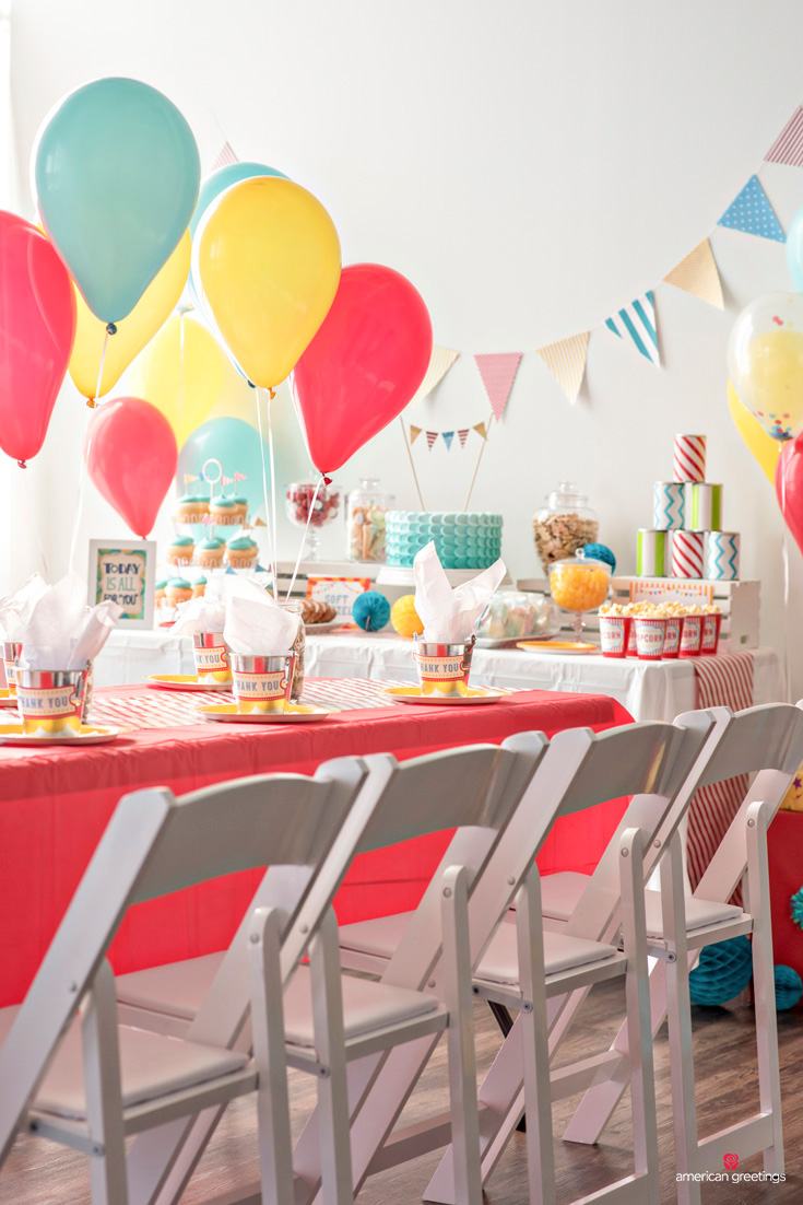 white chairs at table with party favors placed in metal mini-buckets filled with tissue paper