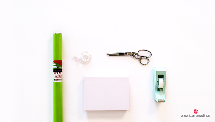 Supplies you'll need: a gift box, tape, double-sided tape, scissors, reversible wrapping paper.