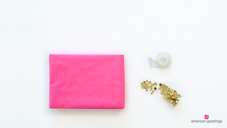 Supplies you'll need: a wrapped present, double sided tape, sequins