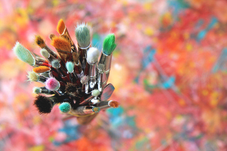 Gift yourself - Try something new - overhead view of colorful paintbrushes