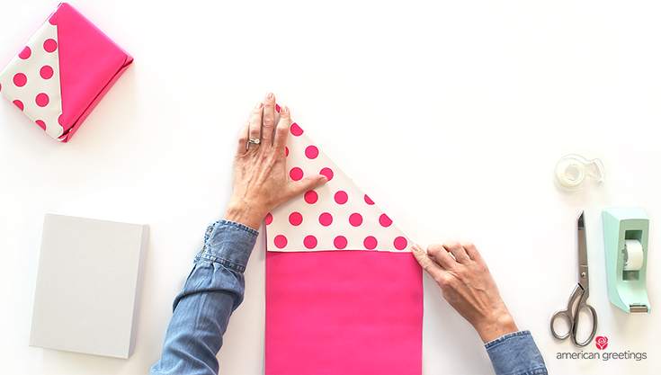 Step 1 illustrated with hands folding down a pink paper with dots at a 45-degree angle