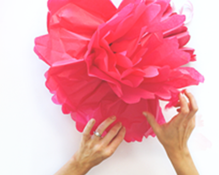 Hands making tissue paper pom poms